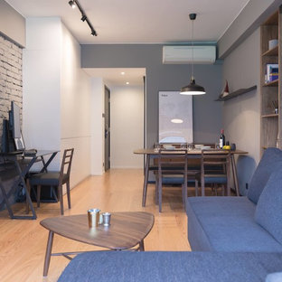 This is an example of a small industrial living room in Hong Kong with grey walls, plywood flooring and a wall mounted tv.