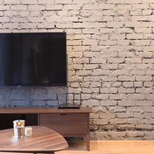 Imagen de salón urbano, pequeño, con paredes grises, suelo de contrachapado y televisor colgado en la pared