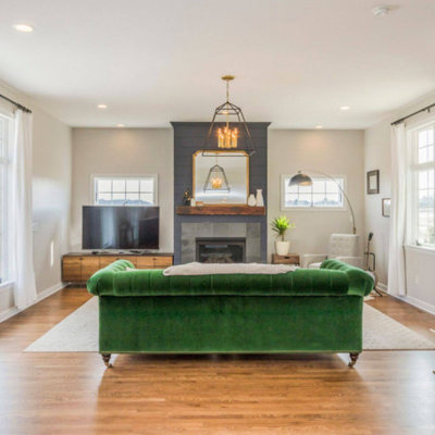 Inspiration for a mid-sized transitional formal and open concept medium tone wood floor and brown floor living room remodel in Cedar Rapids with white walls, a standard fireplace, a tile fireplace and a tv stand