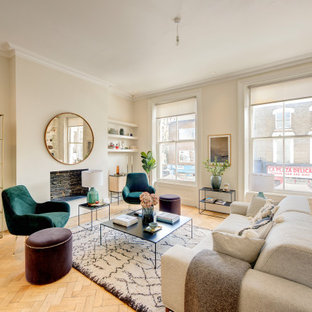 Classic formal open plan living room in London with white walls, medium hardwood flooring, a standard fireplace, a brick fireplace surround, no tv and brown floors.