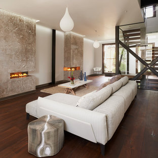 Inspiration for a contemporary dark wood floor living room remodel in London with a two-sided fireplace, a plaster fireplace, white walls and no tv