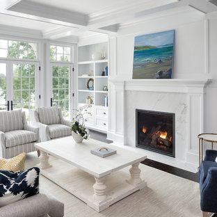 ミネアポリスのビーチスタイルのおしゃれなリビング (白い壁、濃色無垢フローリング、標準型暖炉、石材の暖炉まわり、茶色い床) の写真