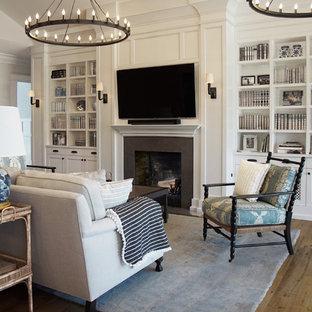 Klassisk inredning av ett stort allrum med öppen planlösning, med ett bibliotek, vita väggar, mellanmörkt trägolv, en standard öppen spis, en spiselkrans i sten, en väggmonterad TV och brunt golv