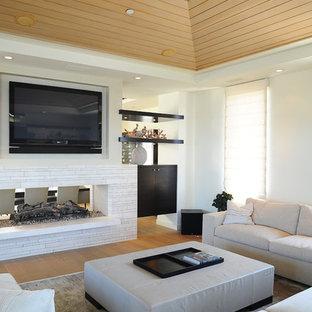 ロサンゼルスのビーチスタイルのおしゃれなリビング (白い壁、両方向型暖炉、壁掛け型テレビ) の写真