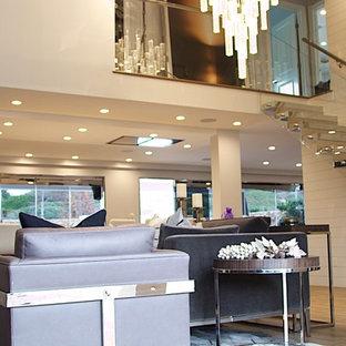 Immagine di un soggiorno minimalista di medie dimensioni e stile loft con sala formale, pareti bianche, pavimento in legno massello medio, camino classico, cornice del camino in pietra, TV a parete e pavimento marrone