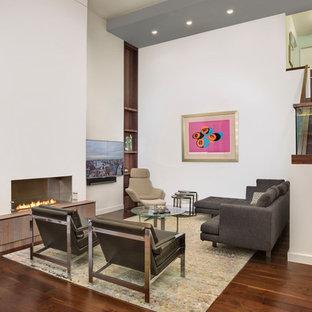 Inspiration för ett stort funkis allrum med öppen planlösning, med vita väggar, mörkt trägolv, en bred öppen spis, en väggmonterad TV, en spiselkrans i gips, ett finrum och brunt golv
