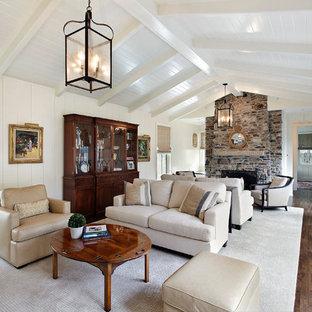 Imagen de salón tradicional, grande, con paredes blancas, chimenea tradicional y marco de chimenea de piedra