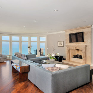 Example of a mid-sized transitional open concept and formal medium tone wood floor and brown floor living room design in Chicago with gray walls, a standard fireplace, a wall-mounted tv and a tile fireplace