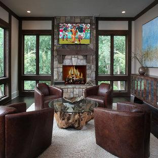 Imagen de salón para visitas cerrado, rural, de tamaño medio, con suelo de madera oscura, chimenea tradicional, marco de chimenea de piedra y televisor colgado en la pared