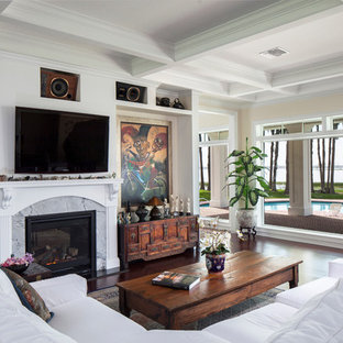 Example of a mid-sized classic open concept dark wood floor living room design in Orlando with beige walls, a standard fireplace, a stone fireplace and a wall-mounted tv