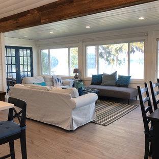 他の地域の中サイズのビーチスタイルのおしゃれなLDK (白い壁、ラミネートの床、薪ストーブ、タイルの暖炉まわり、壁掛け型テレビ、グレーの床) の写真