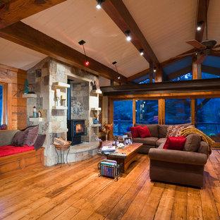 Esempio di un soggiorno stile rurale di medie dimensioni e aperto con pareti marroni, pavimento in legno massello medio, stufa a legna, cornice del camino in pietra, nessuna TV e sala formale
