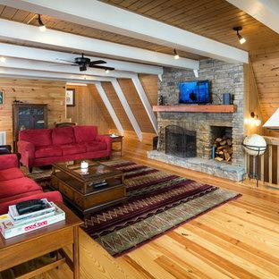 Bild på ett rustikt allrum med öppen planlösning, med bruna väggar, ljust trägolv, en standard öppen spis, en spiselkrans i sten och en väggmonterad TV