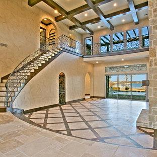 ダラスの巨大な地中海スタイルのおしゃれなLDK (ベージュの壁、トラバーチンの床、標準型暖炉、石材の暖炉まわり、フォーマル) の写真