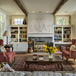 Lantlig inredning av ett vardagsrum, med en standard öppen spis, en spiselkrans i sten och grå väggar