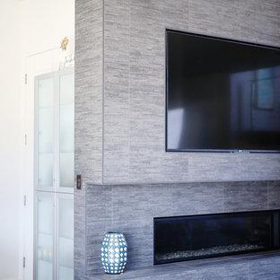 Ejemplo de salón para visitas abierto, actual, grande, con paredes grises, suelo vinílico, chimenea tradicional, marco de chimenea de baldosas y/o azulejos, pared multimedia y suelo marrón