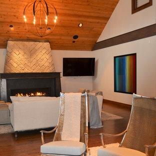 シアトルの大きいインダストリアルスタイルのおしゃれなLDK (フォーマル、ベージュの壁、無垢フローリング、標準型暖炉、金属の暖炉まわり、壁掛け型テレビ、茶色い床) の写真