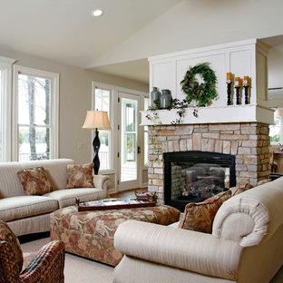 グランドラピッズの大きいトラディショナルスタイルのおしゃれなLDK (石材の暖炉まわり、フォーマル、ベージュの壁、濃色無垢フローリング、両方向型暖炉、テレビなし、茶色い床) の写真