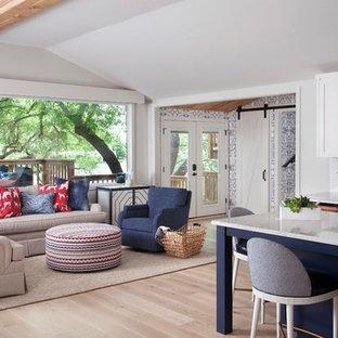オースティンの中くらいのビーチスタイルのおしゃれなLDK (グレーの壁、淡色無垢フローリング、標準型暖炉、石材の暖炉まわり、壁掛け型テレビ、茶色い床) の写真