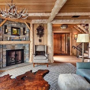 Diseño de salón rural con paredes beige, chimenea de esquina, marco de chimenea de piedra y suelo marrón