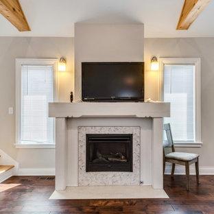 Modelo de salón abierto, moderno, con paredes beige, suelo de madera en tonos medios, chimenea tradicional, marco de chimenea de baldosas y/o azulejos y suelo marrón