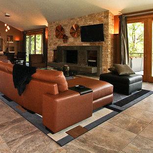 Modelo de salón para visitas abierto, moderno, grande, con paredes marrones, suelo de baldosas de cerámica, chimenea tradicional, marco de chimenea de piedra y televisor colgado en la pared