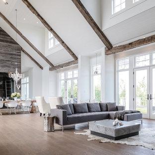 トロントの巨大なビーチスタイルのおしゃれなLDK (白い壁、無垢フローリング、標準型暖炉、木材の暖炉まわり) の写真