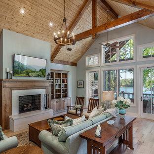 Réalisation d'un salon chalet fermé avec un bar de salon, un mur bleu, un sol en bois clair, une cheminée standard, un manteau de cheminée en béton, un téléviseur fixé au mur et un sol beige.