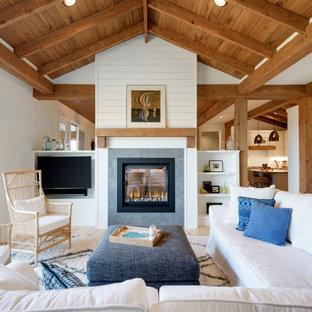 Modelo de salón abierto, campestre, de tamaño medio, con paredes blancas, suelo de madera clara, chimenea de doble cara, marco de chimenea de hormigón, televisor en una esquina y suelo marrón