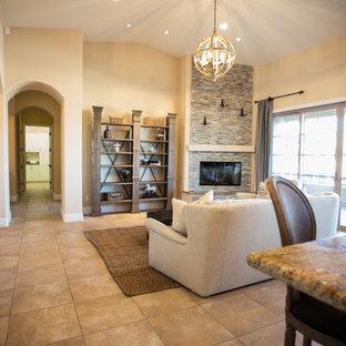 ラスベガスの中サイズのビーチスタイルのおしゃれなLDK (ベージュの壁、テラコッタタイルの床、吊り下げ式暖炉、石材の暖炉まわり、テレビなし、茶色い床) の写真