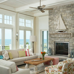 Coastal living room photo in Grand Rapids with beige walls, a standard fireplace and a stone fireplace