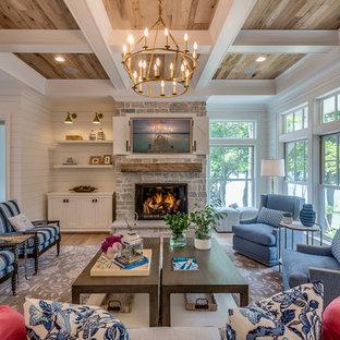 Esempio di un soggiorno country con sala formale, pareti bianche, parquet chiaro, camino classico, cornice del camino in pietra e TV nascosta