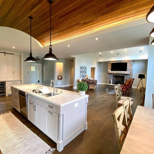 Arts and crafts dark wood floor, brown floor, wood ceiling and shiplap wall living room photo in Other with gray walls, a standard fireplace, a stone fireplace and a wall-mounted tv