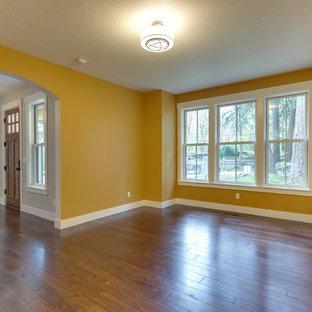 ポートランドの広いトランジショナルスタイルのおしゃれな独立型リビング (フォーマル、黄色い壁、濃色無垢フローリング、暖炉なし、テレビなし、茶色い床) の写真