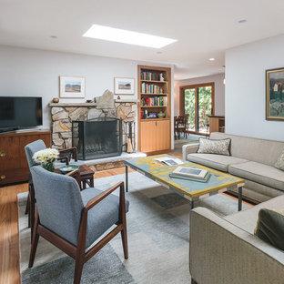 ポートランドのミッドセンチュリースタイルのおしゃれな独立型リビング (白い壁、無垢フローリング、標準型暖炉、石材の暖炉まわり、据え置き型テレビ、茶色い床) の写真