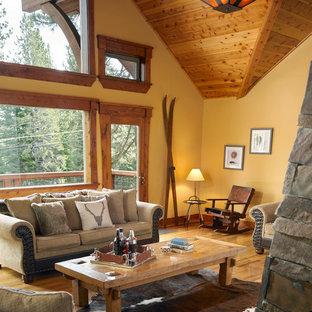 Imagen de salón abierto, rural, grande, con paredes amarillas, suelo de madera en tonos medios y marco de chimenea de piedra