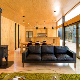 Idee per un soggiorno country aperto con pavimento in compensato e stufa a legna