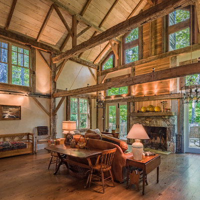 Mountain style open concept medium tone wood floor living room photo in Other with beige walls, a standard fireplace and a stone fireplace