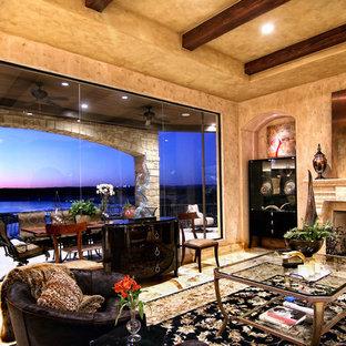 Idee per un grande soggiorno mediterraneo aperto con sala formale, pareti multicolore, pavimento in travertino, camino classico e nessuna TV