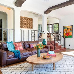 Immagine di un grande soggiorno mediterraneo aperto con sala formale, pareti beige, pavimento in legno massello medio, camino classico, cornice del camino in mattoni e nessuna TV