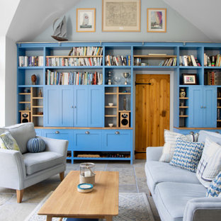 This is an example of a classic living room in Other with white walls, a concealed tv, grey floors and a vaulted ceiling.