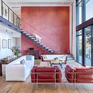 Living room - large modern open concept light wood floor living room idea in Austin with red walls