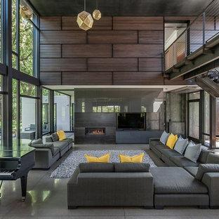 Foto de salón contemporáneo con paredes marrones, suelo de cemento, chimenea lineal, televisor colgado en la pared y suelo gris