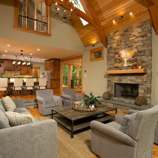 Large rustic formal open plan living room in DC Metro with beige walls, medium hardwood flooring, a stone fireplace surround, a wall mounted tv, a standard fireplace and brown floors.