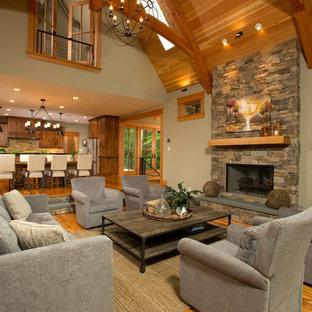 Modelo de salón para visitas abierto, rústico, grande, con paredes beige, suelo de madera en tonos medios, marco de chimenea de piedra, televisor colgado en la pared, chimenea tradicional y suelo marrón