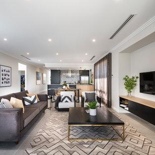 Modelo de salón abierto, actual, de tamaño medio, con paredes blancas, suelo de baldosas de porcelana, televisor colgado en la pared y suelo gris