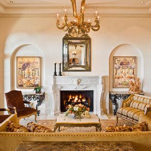 オースティンの広い地中海スタイルのおしゃれな独立型リビング (フォーマル、標準型暖炉、テレビなし、大理石の床、ベージュの壁、木材の暖炉まわり、茶色い床) の写真
