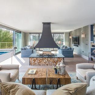 Idéer för ett modernt allrum med öppen planlösning, med ett finrum, gröna väggar, mellanmörkt trägolv, en väggmonterad TV, en dubbelsidig öppen spis och brunt golv