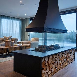 Esempio di un soggiorno contemporaneo aperto con sala formale, pavimento in legno massello medio, camino bifacciale e pavimento marrone