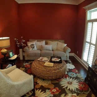Example of a small arts and crafts enclosed dark wood floor and brown floor living room library design in Little Rock with red walls and no tv